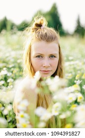 Portrait of a red-haired girl among a chamomile field