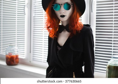 Portrait of red-haired girl in bow tie on a dark background, gothic style girl in black clothes, sense style fashion, girl in a black cloak, coat, black lips, round glasses hat, blinds on the balcony