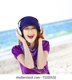 Portrait of red-haired girl in cap with headphone on the beach.
