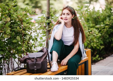 Portrait of a red-haired girl in the city on bench