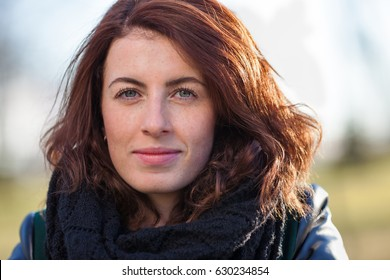 Portrait of a red-haired girl on the street. She looks forward and looks confidently