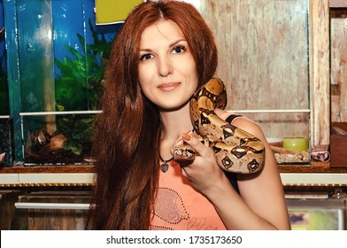Portrait of red-haired girl with Royal Python snake. Woman holds on shoulder and in hand in a contact zoo.