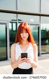 Portrait of red-haired girl using her mobile phone