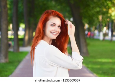 Portrait of red-haired girl in white shirt with long foxy hair posing in park background. Ginger teenager holds her hand near the head and smiling looking at camera.