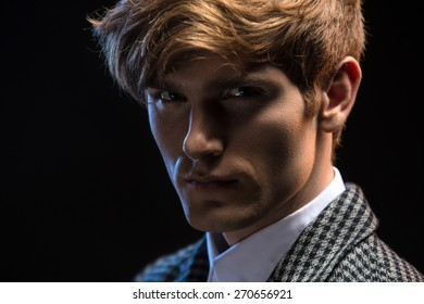 Portrait of red-haired handsome guy on a black background