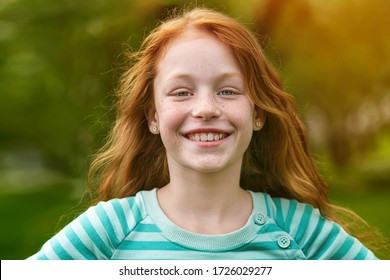 Portrait of a red-haired smiling girl on a background of green grass in the park