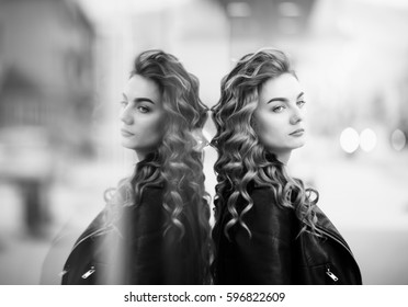 portrait of red-haired woman with the reflection in the window of a shopping mall,black and white photography