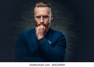 Portrait of redhead bearded hipster male dressed in a blue jacket over grey background.