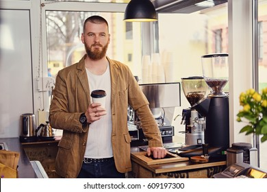 Portrait of redhead bearded male in a small cafe with a lot of flowers and coffee machine.
