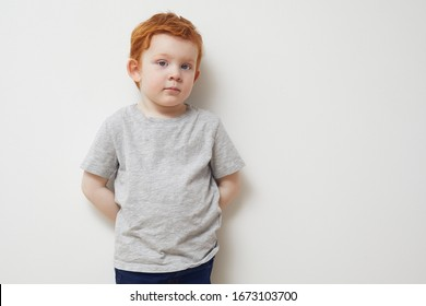 Portrait of redhead boy standing agianst a white wall