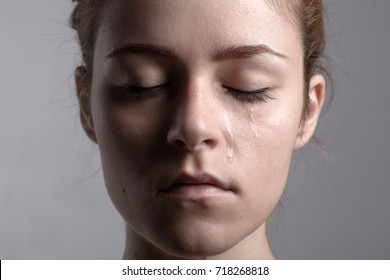 Portrait of a Redhead Crying Woman with Closed Eyes