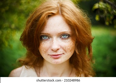 Portrait of redhead girl with blue eyes on nature. Face of young woman with freckles closeup