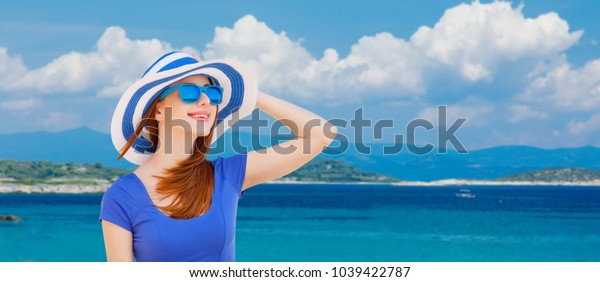 Portrait of redhead girl in hat and sunglasses on blue sky and sea background