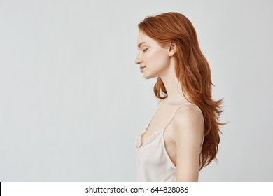 Portrait of redhead girl in profile with closed eyes smiling.