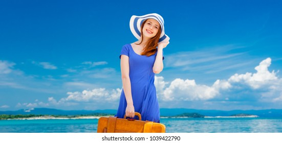 Portrait of redhead girl with suitcase on the beach in summertime. Travel concept