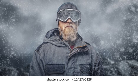 Portrait of a redhead snowboarder with a full beard in a winter hat and protective glasses dressed in a snowboarding coat posing at a studio, looking away.