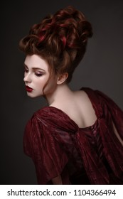 Portrait of redhead woman with baroque hairstyle and evening maroon dress