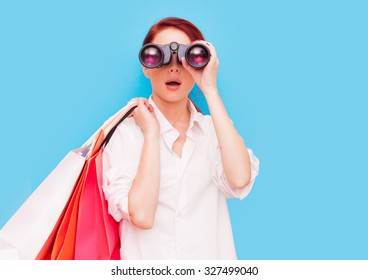 Portrait of a redhead woman with shopping bags and binocular on blue background