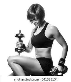 Portrait of redhead young female athlete sitting and holding dumbbells. Studio shot, isolated, white background