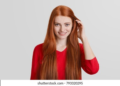 Portrait of redhead young female with long hair, has freckled face, pleasant smile, touches hair, isolated over white background. Ginger woman poses in studio, happy be photograhed.