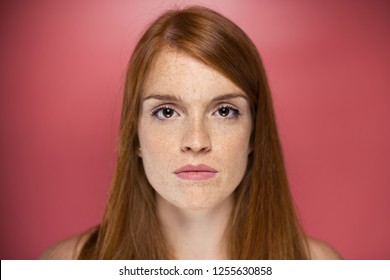 Portrait of redhead young serious woman looking at camera over pink background.