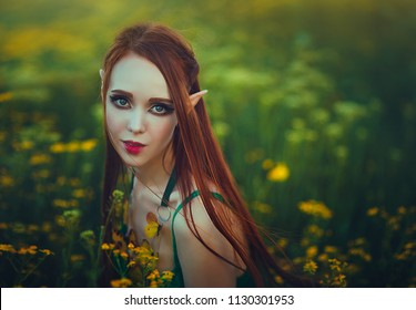 Portrait of a redheaded girl elf in a green swimsuit posing in a clearing of yellow flowers. Fantastic young woman with yellow butterflies in the rays of light.
