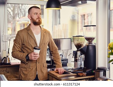 Portrait of redheads craft coffee seller holds a glass of coffee in a small street cafe.
