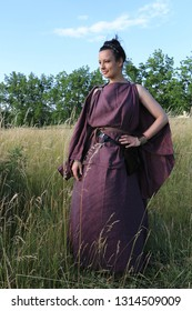 Portrait of a reenacting woman clothed in antique roman or greek burgundy peplum made from linen and leather accessoires