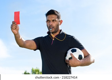 Portrait of referee with a ball showing red card and whistling