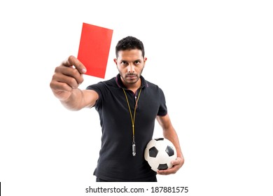 Portrait of referee holding ball and red card