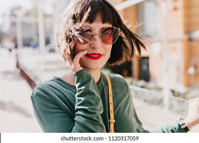 Portrait of refined european girl posing in windy spring day. Outdoor shot of adorable brunette lady in sunglasses and green clothes.