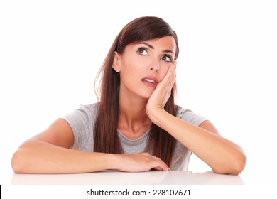 Portrait of reflective woman wondering while looking up on isolated white background - copyspace