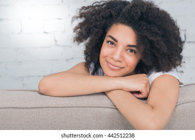 Portrait of relaxed African woman sitting at home smiling confidently at the camera