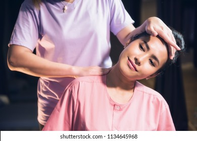 portrait of relaxed Asian beautiful woman massaging neck and shoulder by professional massager in spa salon. Body care treatment by Thai massage. Cute girl with traditional dress.