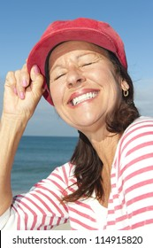 Portrait of relaxed and attractive looking senior woman enjoying active retirement and leisure time at sea, isolated with ocean and blue sky as background and copy space.