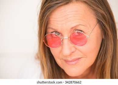 Portrait relaxed attractive mature woman with confident happy look, red glasses, serious friendly facial expression, bright background.