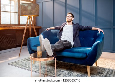 Portrait of relaxed businessman dressed casualy sitting on the couch at the luxury office with blue walls
