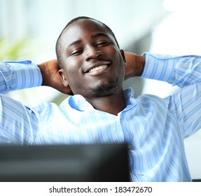 Portrait of a relaxed businessman looking away. african american businessman daydreaming in office
