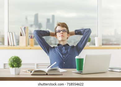 Portrait of relaxed businessman working on project at modern desk with laptop, paperwork, supplies, coffee cup and other items