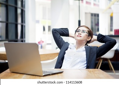 Portrait of relaxed businesswoman with laptop computer at cafe