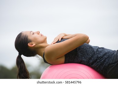 Portrait relaxed concentrated young active attractive woman doing core muscle exercises on fit-ball outdoor, copy space.