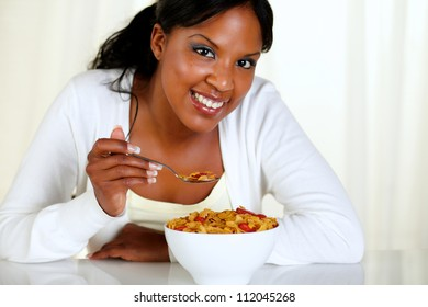 Portrait of a relaxed female looking at you and having breakfast at soft colors composition