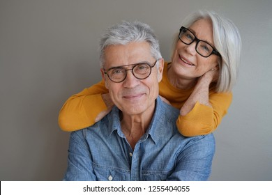 Portrait of relaxed fun senior couple wearing glasses on background                               - Shutterstock ID 1255404055