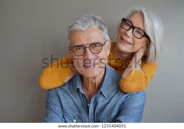 Portrait von entspanntem unterhaltsamem Ehepaar mit Brille auf Hintergrund