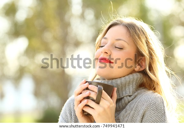 Portrait of a relaxed girl wearing jersey holding a cup of coffee and breathing outdoors in a park in winter