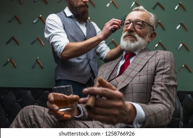 Portrait of relaxed grey haired businessman with sigar and alcoholic beverage having his hair trimmed in a barber shop, low angle. Concept of grooming