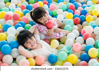 Portrait of relaxed little sisters lying among colorful balls