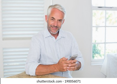 Portrait of a relaxed mature man text messaging at home