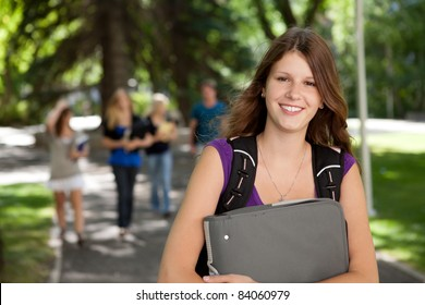 Portrait of a relaxed pretty college girl with binder