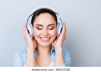 Portrait of relaxed pretty woman listening to music in headphones  isolated gray background.